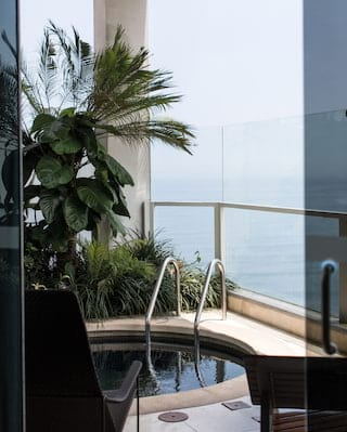 View through glass doors to a balcony plunge pool overlooking the Pacific Ocean