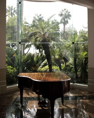 Polished grand piano dappled with palm leaf shadows from the windows beyond