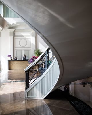 Curved floating stairway leading from a polished marble floored lobby