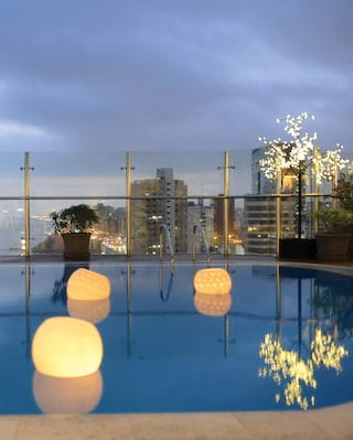 View of floating lanterns on an outdoor pool on the top floor of a Lima hotel