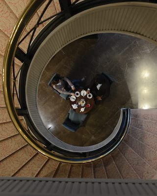 Birds-eye-view of guests having coffee at the bottom of a spiral staircase