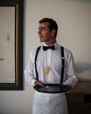 Sommelier wearing a black bow-tie and white shirt, carrying a glass of white wine