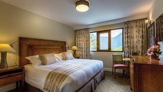 Huge bed with hardwood frame in an elegant sage-hued hotel room