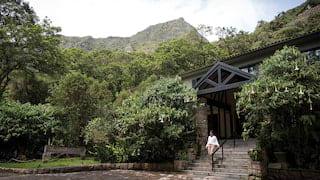 Lady walking down steps from a stone-built veranda in Machu Picchu