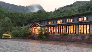 Glowing stone built hotel at dusk, surrounded by jungle and mountains