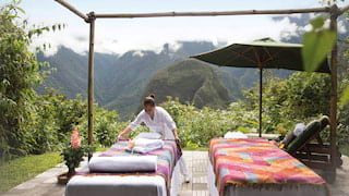 Spa therapist preparing an outdoor massage table overlooking clouded mountains