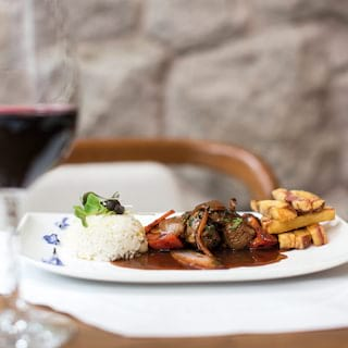 Close-up of contemporary Peruvian cuisine served with a glass of red wine