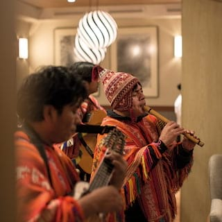 Peruvian musicians in traditional Peruvian dress playing pipes and a guitar