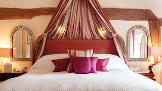 Pillowy bed flanked by two arched mirrors with an assortment of pink cushions