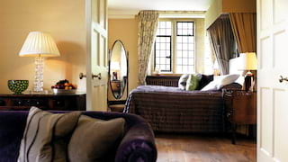Hotel suite with polished wood floors and deep-purple velvet furnishings