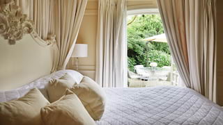 Pillowy four-poster bed with a view through patio doors to a garden area beyond