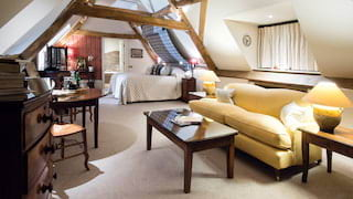 Spacious attic hotel room with wood-beamed ceiling and large yellow sofa