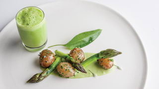 Close-up of an asparagus dish with green foam dressing on the side
