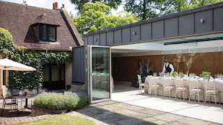 Contemporary glass-walled annex set for a wedding on a sunny day