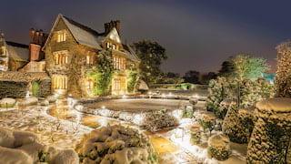 Belmond Le Manoir aux Quat'Saisons and gardens coated in snow in evening light