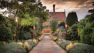 Stone-paved candlelit path leading to a rural manor house in evening light