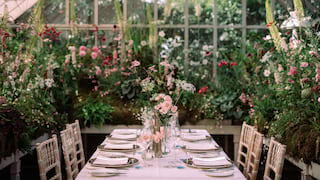 Wedding banquet table in a glass greenhouse filled with pink and white wildflowers