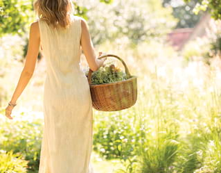 a woman in a cream dress walking through a field holding a basket of flowers