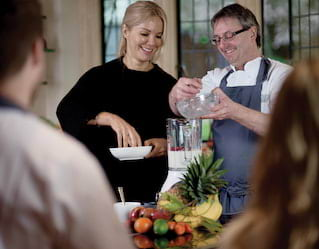 Cookery school instructor and student adding ingredients to a blender