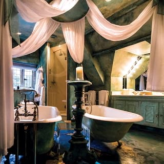 Bathroom with two stand alone bathtubs, decorated in an ornate baroque style