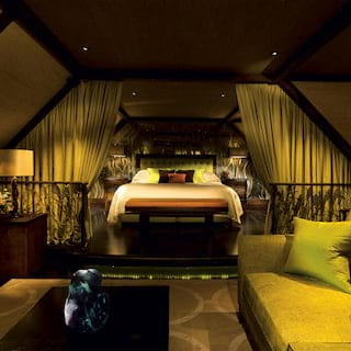 Luxe hotel suite with large bed and lounge area in vibrant green decor