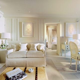 Light and airy hotel room with spacious lounge area entirely decorated in white