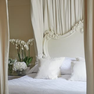 View through four-poster curtains of an ornate white-framed pillowy bed