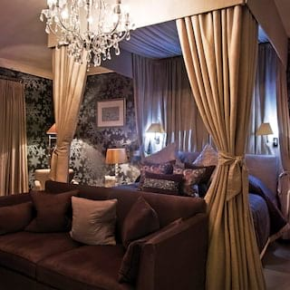 Glamorous suite with crystal chandelier, four-poster bed and snowflake wallpaper