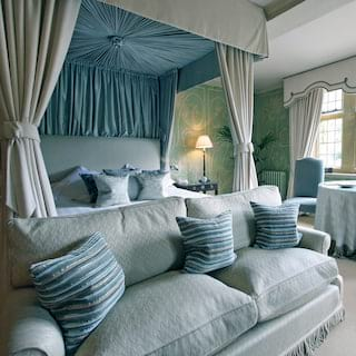 Luxurious hotel suite with four-poster bed and cool blue accents