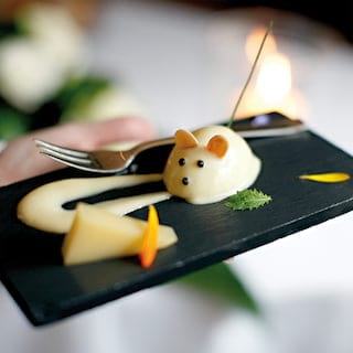 Close-up of a cheese-mousse in the shape of a mouse on a black slate