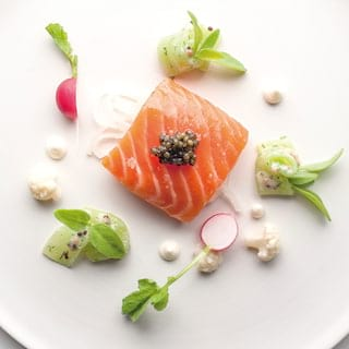 Birds-eye-view of a smoked salmon dish garnished with caviar and radishes