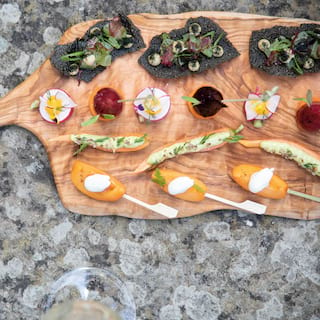Wooden platter with a selection of canapés garnished with edible flowers