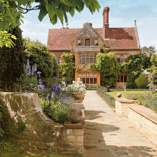 Stone path leading to a vast manor-house with manicured stone-walled gardens