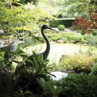 Close-up of a heron bronze statue among maple leaves and lush foliage