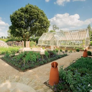 Walled garden divided into vegetable patches with a large glass greenhouse