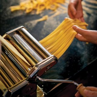 Hands pulling strips of freshly made linguine pasta from a pasta maker