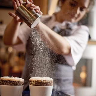 Girl pouring icing sugar from a metal icing sugar shaker