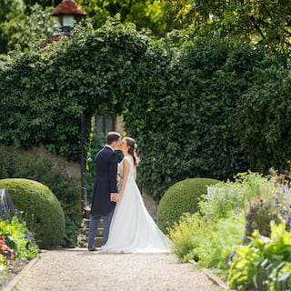 Bride and groom sharing a kiss under an arch in a leafy hedge along a garden path