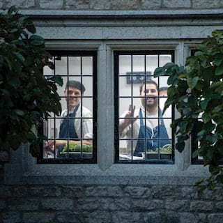 Two smiling chefs viewed through a medieval-style window