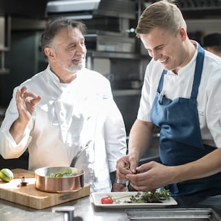 Raymond Blanc smiling as he discusses a recipe with another smiling chef
