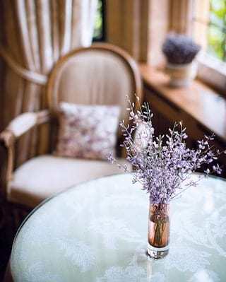 Close-up of a small vase of lavender on a circular glass table