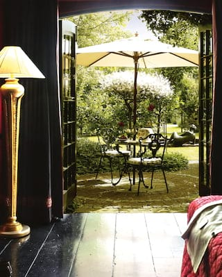 View from a red and black room through patio doors with a seating area beyond