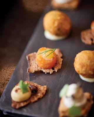 Close-up of a wooden platter with a selection of delectable canapés