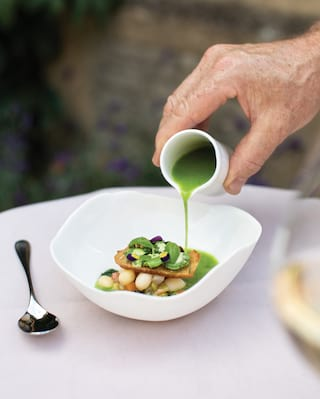Green salad dressing poured into a wavy bowl filled with contemporary cuisine
