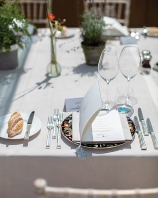 Elegant menu card at a place setting on top of a flower patterned dish