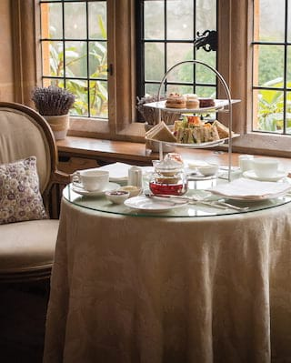 Circular table laden with afternoon tea treats, with two cream chairs either side