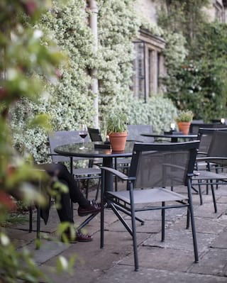 Outdoor patio with black iron tables and chairs with potted plants on top