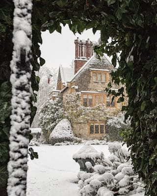 Archway in a leady hedge revealing a snow-coated sandstone manor house