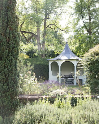 Garden pavilion surrounded by tall hedges in a sunny country garden