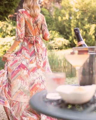 Lady in a summer dress walking away from a table topped with champagne cocktails